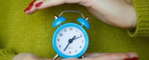 Little blue alarm clock in the hands of women, the concept of saving time